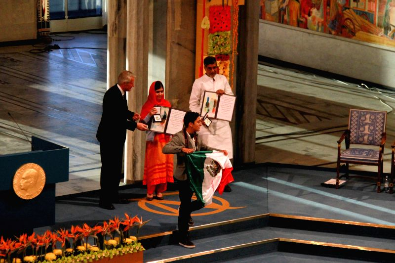Oslo (Norway): A man (front) holding the Mexican flag disturbs the Nobel Peace Prize awarding ceremony in Oslo, Norway, Dec. 10, 2014. Kailash Satyarthi and Malala Yousafzai, two child welfare ...