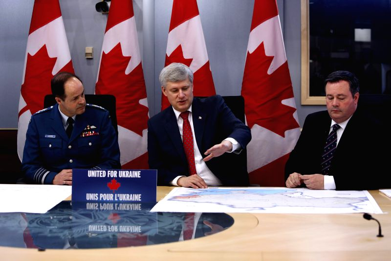 Canadian Prime Minister Stephen Harper (C), Defence Minister Jason Kenney (R) and Chief of the Defence Staff Gen. Thomas Lawson attend a briefing on the current ... - Stephen Harper
