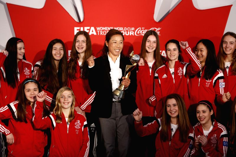 Nozomi Yamago (C) of Japan, the current FIFA World Cup champion team, poses with Canadian soccer youth during a press conference for the FIFA Women's World Cup ...