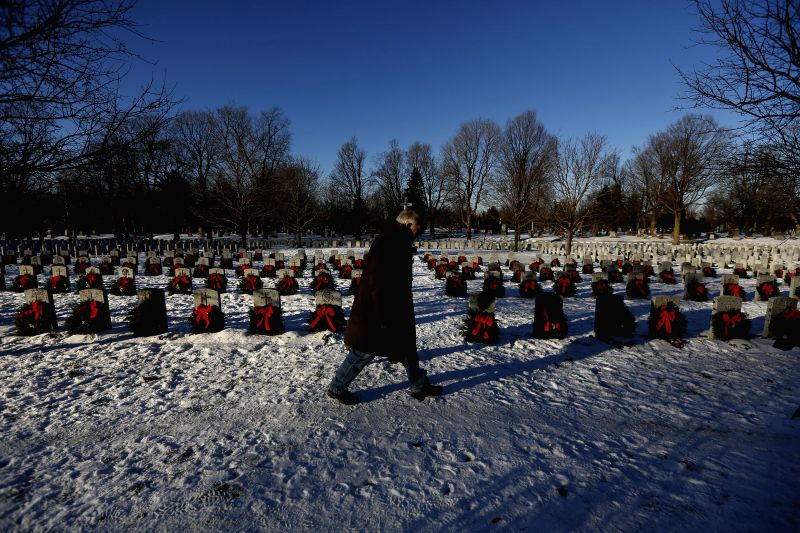 Ottawa (Canada): A man walks among tombstones during the annual Wreaths Across Canada commemoration ceremony at the National Military Cemetery in Ottawa, Canada on Dec. 7, 2014. About 3,000 wreaths ..