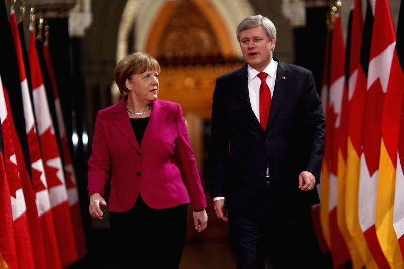 German Chancellor Angela Merkel (L) walks with Canada's Prime Minister Stephen Harper down the Hall of Honour at Parliament Hill in Ottawa, Canada, on Feb. 9, 2015. . - Stephen Harper