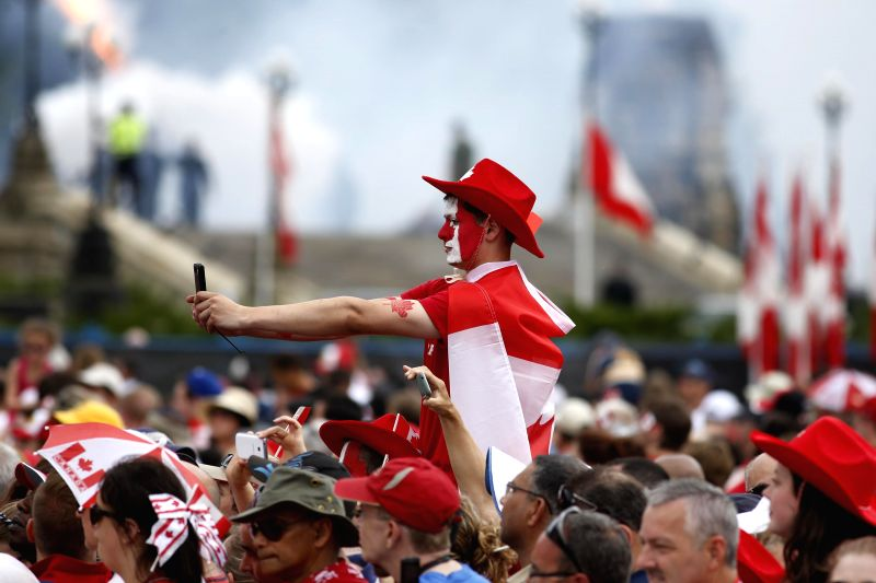 A spectator takes a photo in the background during the ceremonies to celebrate the 147th Canada Day on Parliament Hill in Ottawa, Canada, on July 1, 2014.