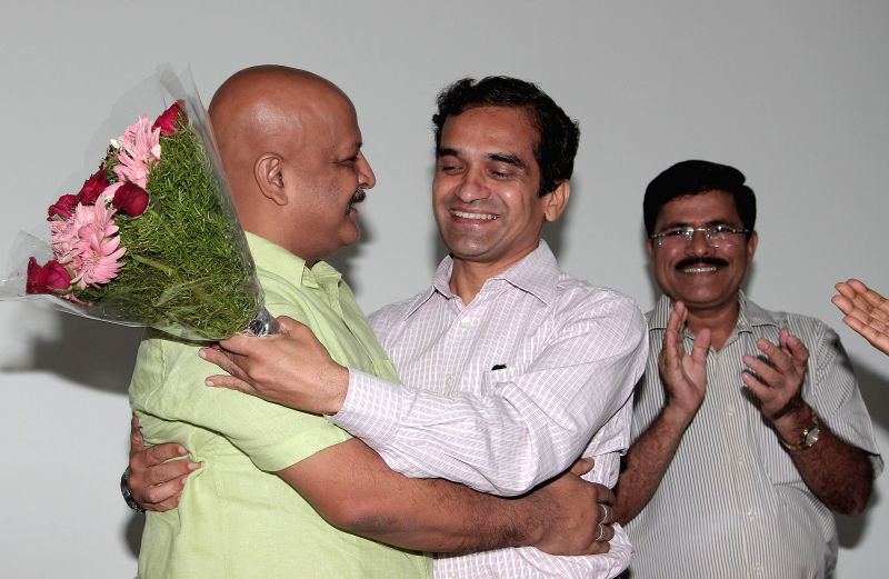 Outgoing Director of FTII DJ Narain greets his successor Prashant Pathrabe in Pune, on July 17, 2015.