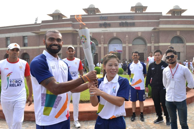 P.R. Sreejesh who will lead the 18-member Indian Men's Hockey Team at the 18th Asian Games, and Indian boxer MC Mary Kom hold the torch of the 18th Asian Games Jakarta-Palembang 2018 as ... - Mary Kom