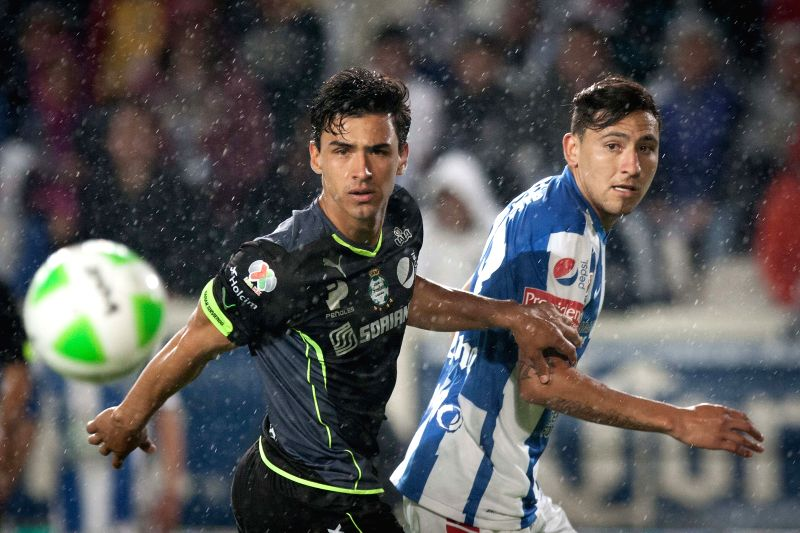 Pachuca's Abraham Carreno (R) vies for the ball with Santos' Oswaldo Alanis (L), during their first leg semifinal match of the Liga MX Closing Tournament at Hidalgo ..