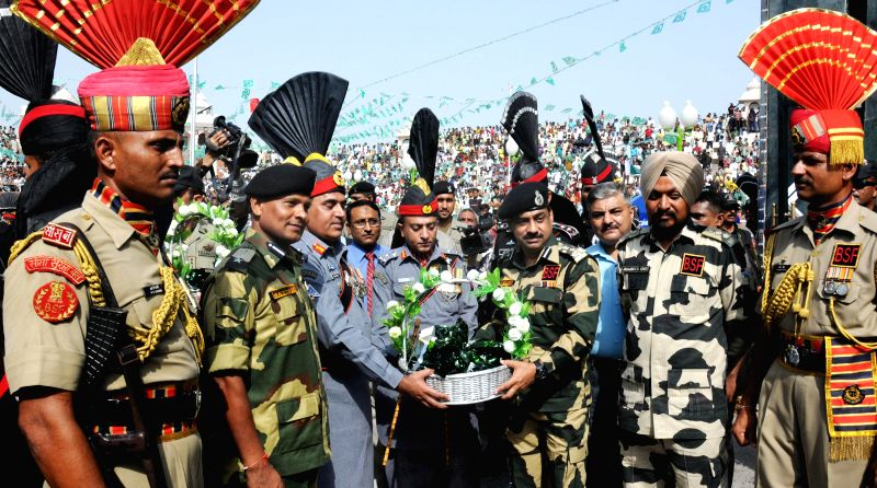 Pakistan Rangers Director General Major General Khan Tahir Javed Khan offers sweets to Border Security Force (BSF) Deputy Inspector General (DIG), M F Farooqui on Pakistani Independence Day at ...