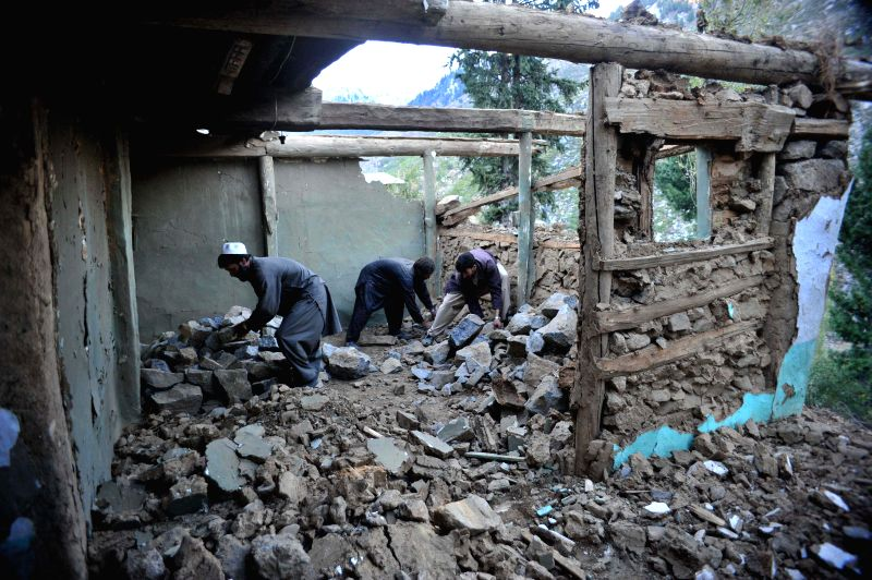 Pakistani men remove debris from their damaged house following an earthquake in northwest Pakistan?s Lower Dir, Oct. 27, 2015. The Red Cross Society of China ...