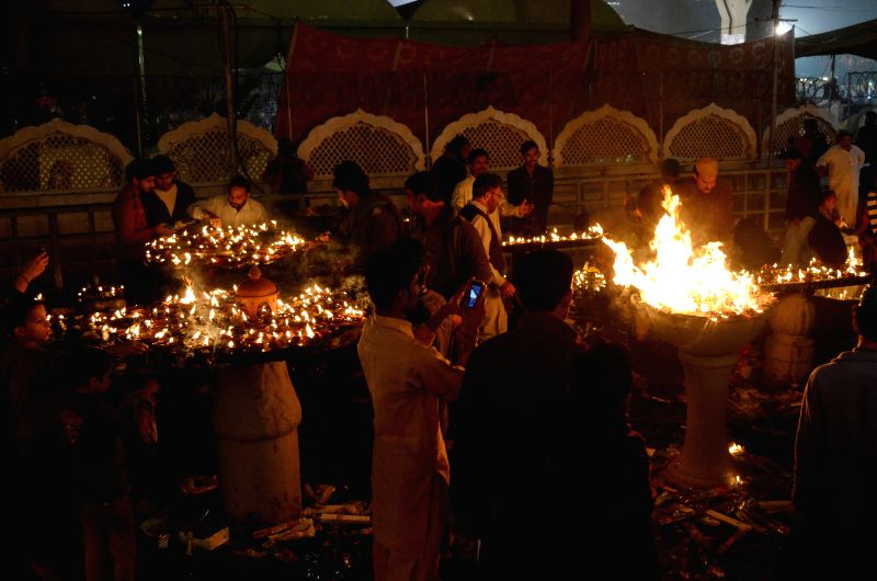 "Pakistani Muslim devotees light oil lamps at the shrine of Hazrat Ali Bin Usman, popularly known as Data Gunj Bakhsh, during the annual ""Urs"" religious ..."