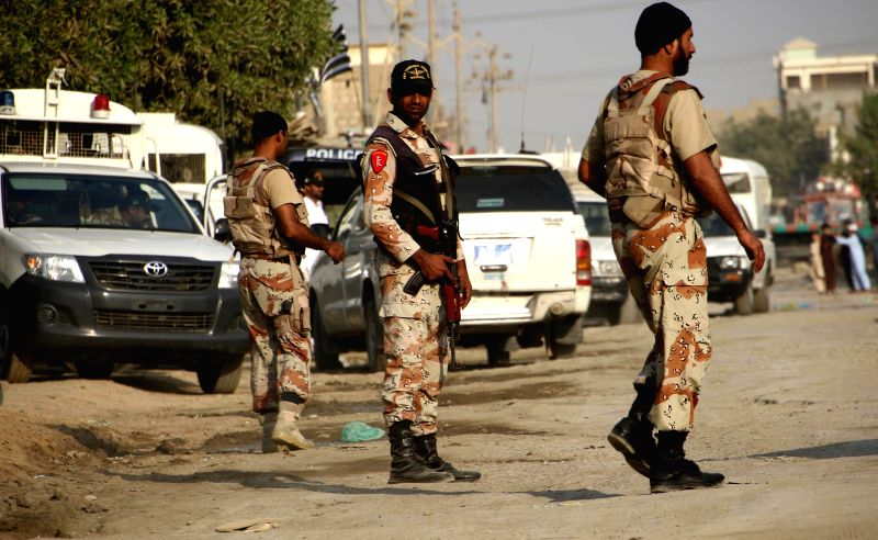 Pakistani security officials stand guard at the attack site in Karachi, Pakistan, Nov. 20, 2015. At least three Paramilitary troops were killed while stopping ...