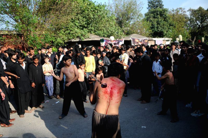 Pakistani Shiite Muslims flagellate themselves during a Muharram procession to mark the Day of Ashura in Islamabad, capital of Pakistan, Oct. 23, 2015. The Day of ...