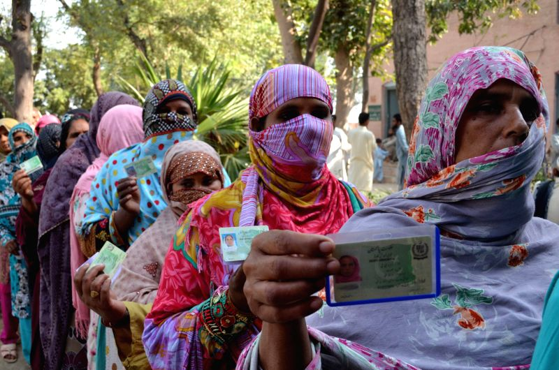 Pakistani women queue to cast their ballots at a polling station during the local government elections in eastern Pakistan's Lahore, on Oct. 31, 2015. The first ...