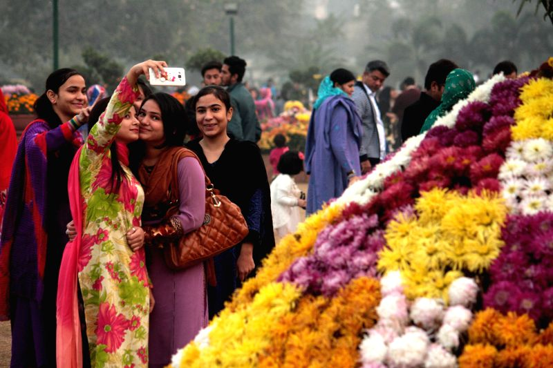 Pakistani women take selfies at an annual autumn flowers show in eastern Pakistan's Lahore, Dec. 10, 2015.