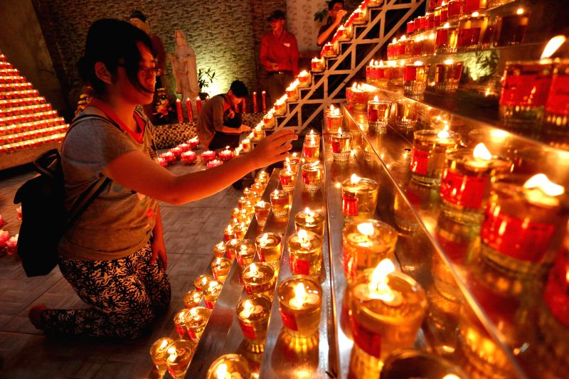 A woman lights candles to pray on the eve of the Chinese Lunar New Year at a temple in Palembang, South Sumatra, Indonesia, Feb. 18, 2015.  (Xinhua/Nova ...