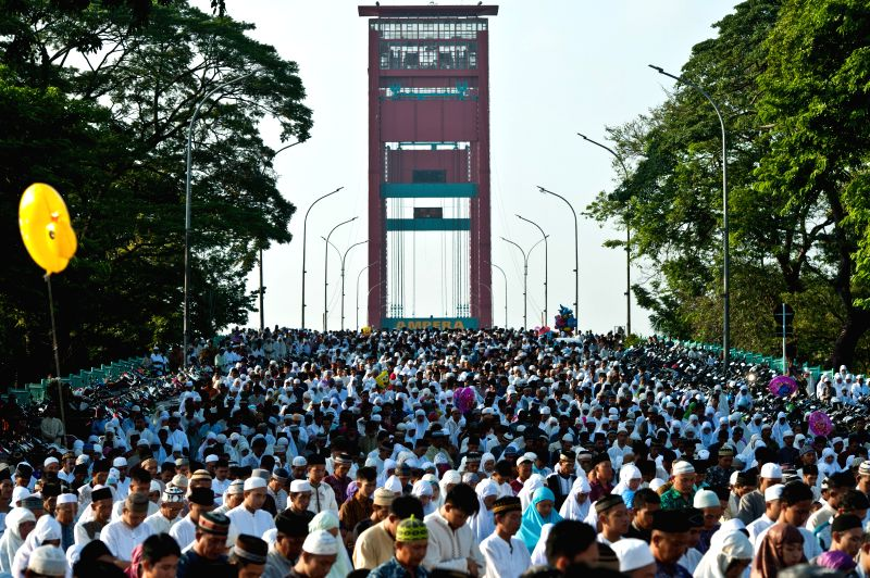 Muslims gather on the main way in front of the Great Mosque Palembang to attend the Eid Al-Fitr celebration in Palembang, South Sumatera Province in Indonesia, on