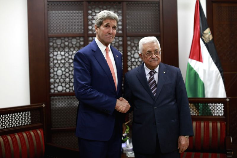 Palestinian President Mahmoud Abbas (R) shakes hands with the U.S. Secretary of State John Kerry upon his arrival to the west bank city of Ramallah on Nov. 24, ...