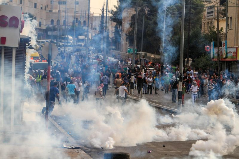 Palestinian protesters run to take cover from gas tear fired by the Israeli soldiers during clashes in the West Bank city of Bethlehem, on Oct. 23, 2015. At least ...