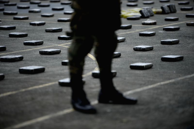 A member of the National Borders Service (SENAFRONT), guards cocaine packages during a press conference in Panama City, capital of Panama, on April 14, 2014. ..
