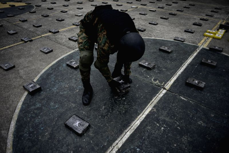 A member of the National Borders Service (SENAFRONT) places cocaine packages during a press conference in Panama City, capital of Panama, on April 14, 2014. ...