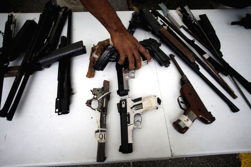 A member of the National Police holds weapons that will be destroyed, in Panama City, capital of Panama, on April 24, 2014. The National Police destroyed over .