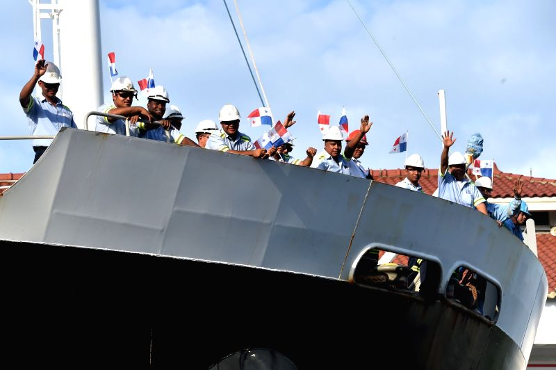 Workers of the Panama Canal Authority wave Panamanian national flags during the commemoration of the 100th anniversary of the Panama Canal, at the Miraflores ...