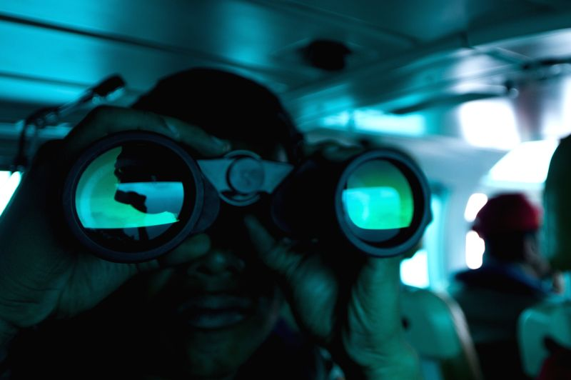 A rescue worker use a telescope while searching the missing AirAsia QZ8501 above the sea between Bangka island and Belitung island in Pangkal Pinang, ...