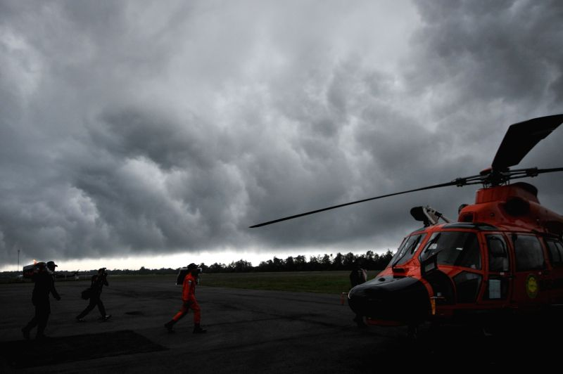 Search and Rescue (SAR) team members bring body bags to helicopter in bad weather at Pangkalan Bun, in Central Kalimantan, Indonesia, Dec. 31, 2014. ...