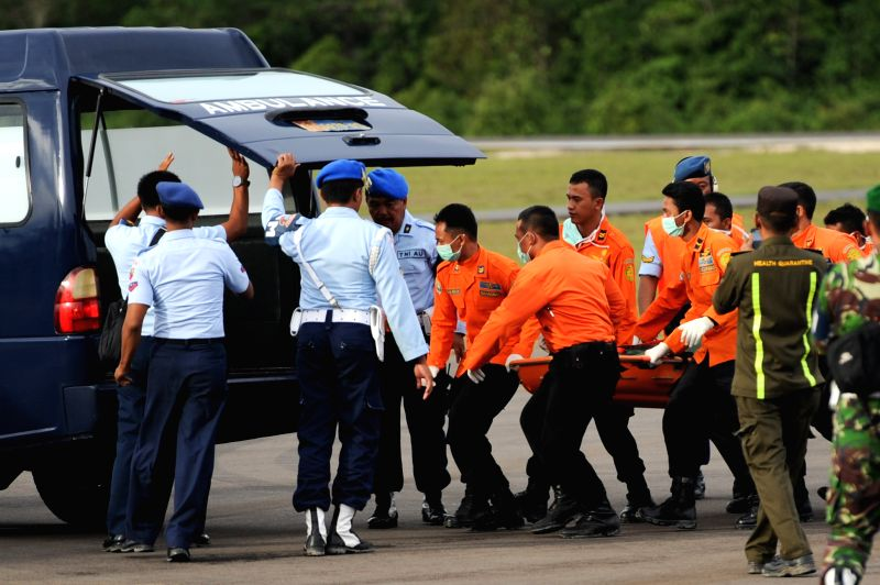 Search and Rescue (SAR) people carry the body bag containing the eighth victim of AirAsia flight QZ8501 to ambulance at Iskandar Air Base in Pangkalan Bun, ...