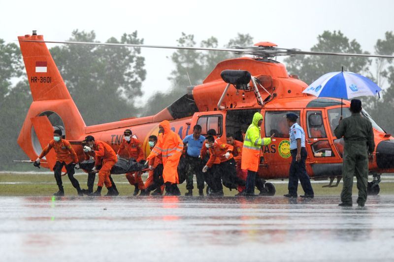 Search and Rescue (SAR) team members move a body bag containing the seventh victim of AirAsia flight QZ8501 from a helicopter at Iskandar Air Base in Pangkalan