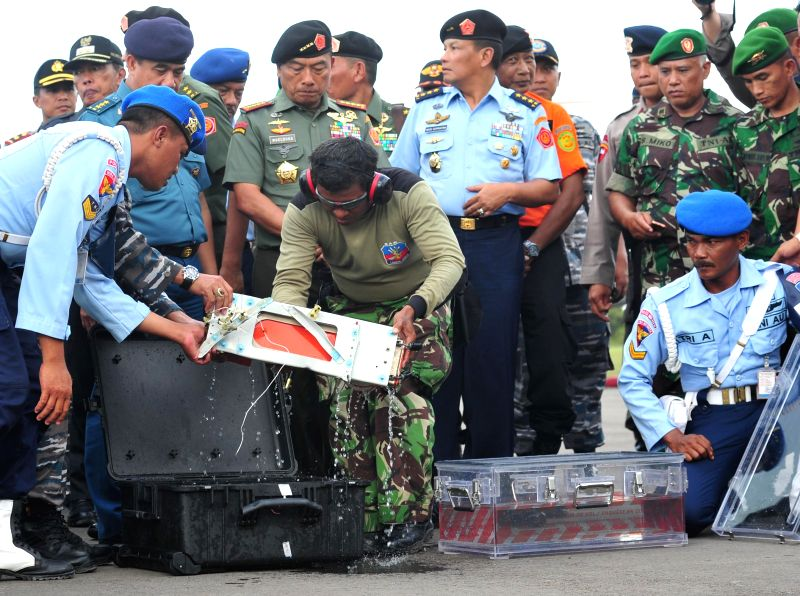 Indonesian Police Military carry the flight data recorder of the AirAsia Flight QZ8501 at Iskandar air base in Pangkalan Bun, Central Borneo, Indonesia, Jan. .