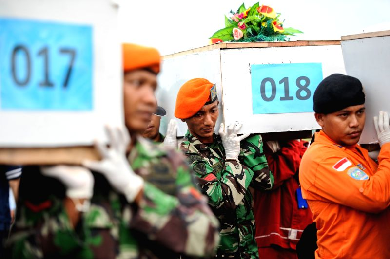 Joint officers carry the coffins that contain victims of AirAsia flight QZ8501 to the aircraft that brings them to Surabaya at Iskandar Air Base, in Pangkalan .