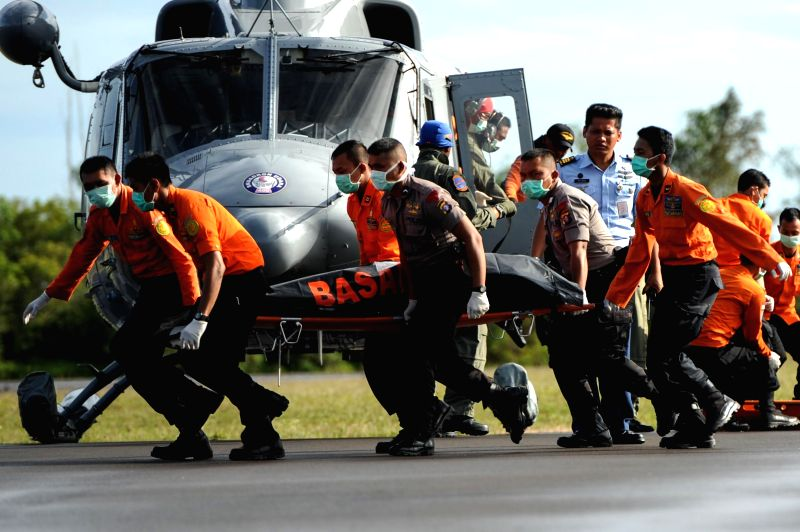 Search and Rescue (SAR) personnel and policemen carry a body bag containing the ninth victim of AirAsia flight QZ8501 from helicopter at Iskandar Air Base, in .