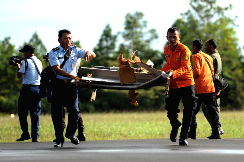 Search and Rescue (SAR) personnel and TNI carry debris of AirAsia flight QZ8501 from helicopter at Iskandar Air Base, in Pangkalan Bun, Central Kalimantan, ...