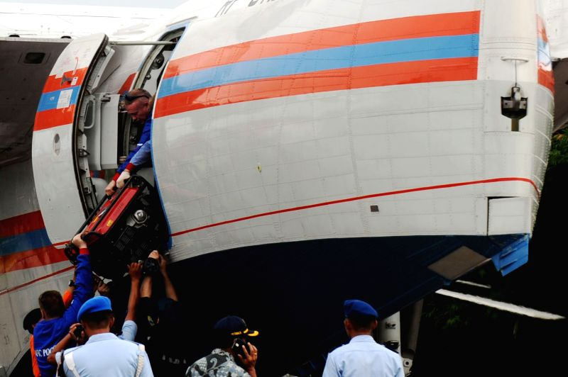Crew members of a Russian amphibious plane unload the luggage after landing on Pangkalan Bun Airport in Pangkalan Bun, Indonesia, Jan. 3, 2015. Supriyadi, ...
