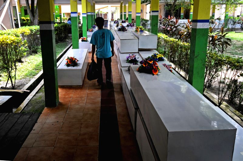 A man walks past coffins of victims of AirAsia Flight QZ8501 at a hospital in Pangkalan Bun, Indonesia. Jan. 4, 2015. An Indonesian pilot taking part in the ...