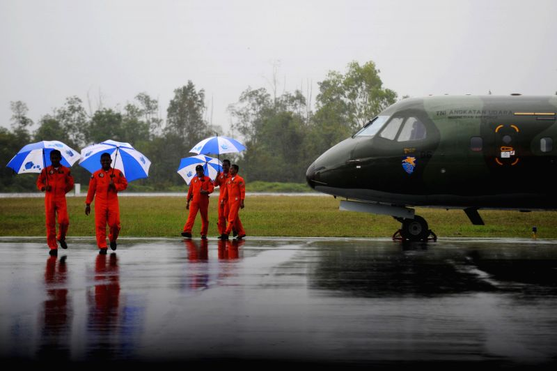 Indonesian air force pilots hold umbrellas during heavy rain while their plane is canceled to fly at Pangkalan Bun, Indonesia, Jan. 4, 2015. The search and ...