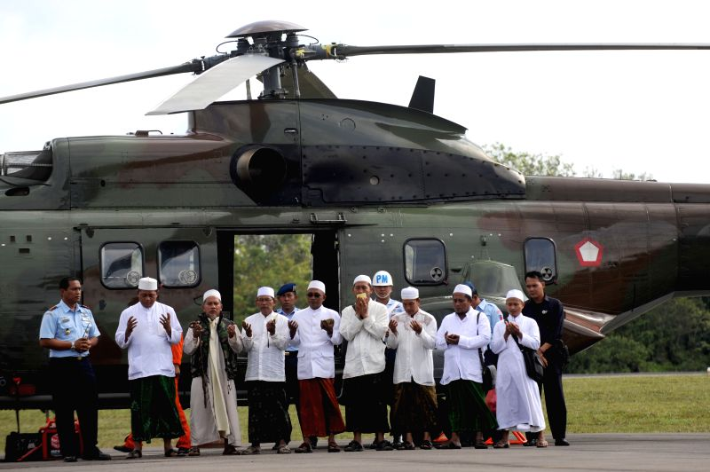 Muslims pray before boarding an Indonesian Air Force NAS 332 Super Puma helicopter to the location of AirAsia QZ8501 on the Java sea to read prayers and sow ...