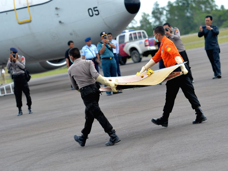 Indonesian rescuers carry the debris of AirAsia flight QZ8501 in Pangkalan Bun, Indonesia, Jan. 9, 2015. Signals from the black boxes of an AirAsia jetliner, ..
