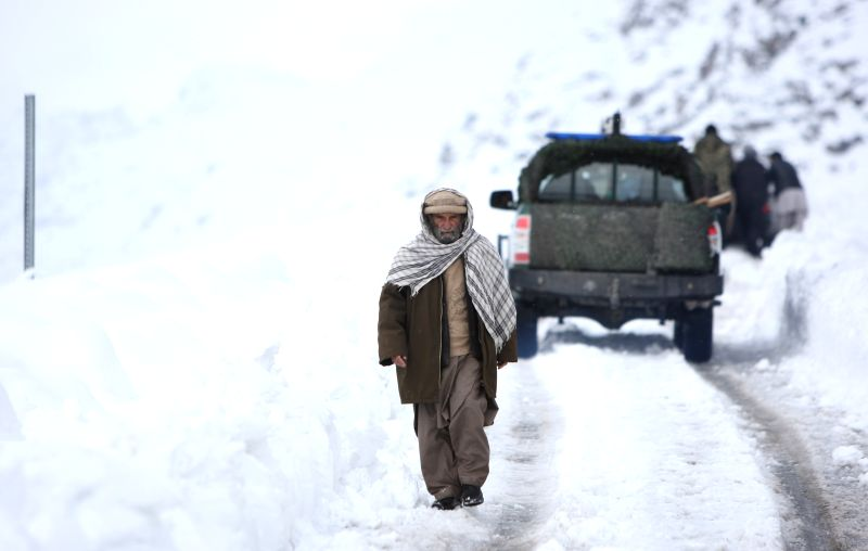 An Afghan man walks in the snow in Panjshir province, east Afghanistan, on Feb. 25, 2015. The death toll has risen to more than 120 while several of others still ...