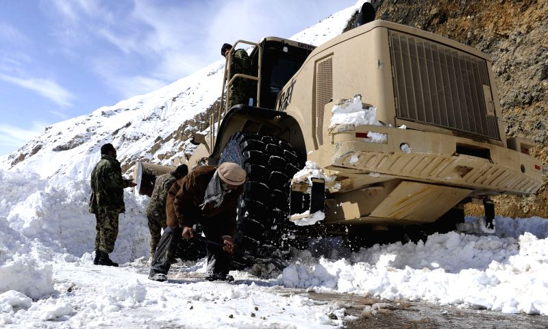 Photo taken on Feb. 28, 2015 shows a digger cleaning up the snow on a road close to the avalanches site in Panjshir province, east Afghanistan. The death toll has ...