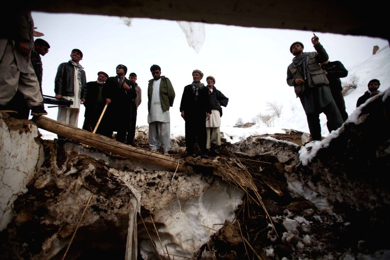 Afghan men remove snow from a damaged house after avalanches in Abdullah Khil of Panjshir province, Afghanistan, on March 1, 2015. Afghan government and scores of ...