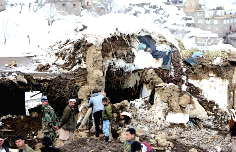 Afghan men remove snow from a damaged house after avalanches in Abdullah Khil of Panjshir province, Afghanistan, March 1, 2015. Afghan government and aid agencies ...