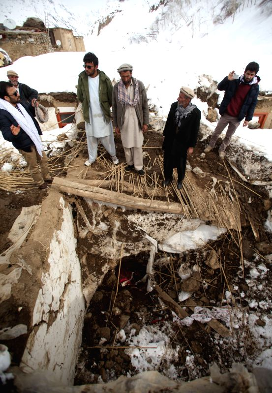 Afghan men stand on a destroyed house after avalanches in Abdullah Khil of Panjshir province, Afghanistan, March 1, 2015. Afghan government and aid agencies have ...