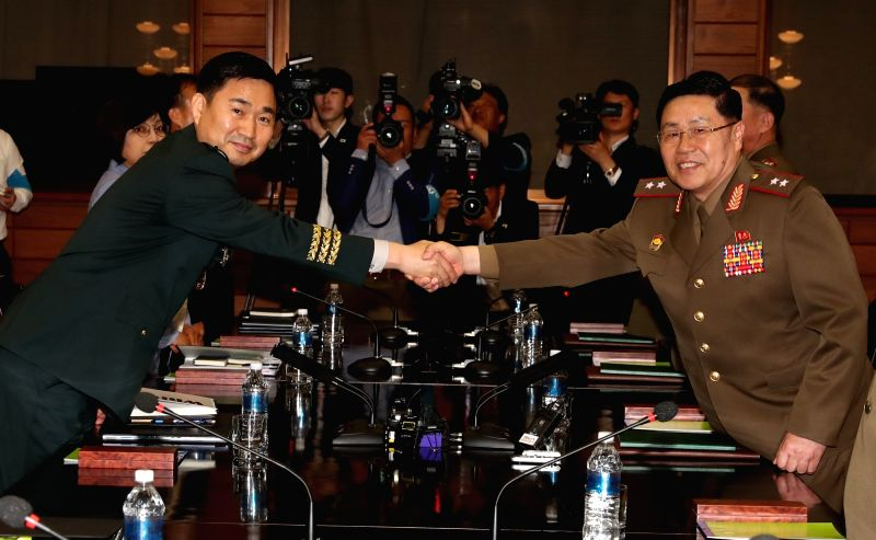 :Panmunjom: South Korea's chief delegate Major Gen. Kim Do-gyun (L) shakes hands with his North Korean counterpart Lt. Gen. An Ik-san during the first high-level inter-Korean military talks in ...