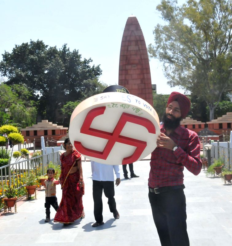 Paper artist Gurpreet Singh spreads a message of Voter Awareness with his creation of 2ft big election stamp replica at Jallianwala Bagh in Amritsar on April 26, 2014. - Gurpreet Singh