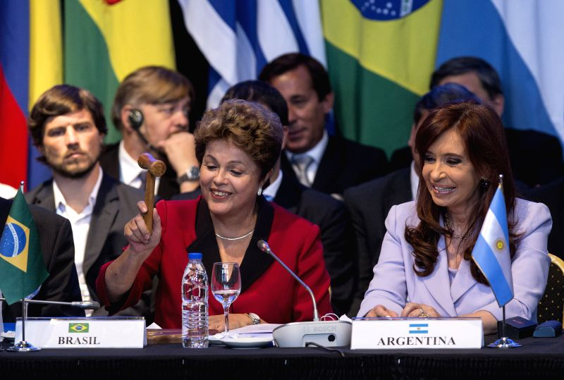 Brazil's President Dilma Rousseff (L) receives the MERCOSUR flag from Argentine counterpart Cristina Fernandez (R) during the 47th Southern Common Market (MERCOSUR) .