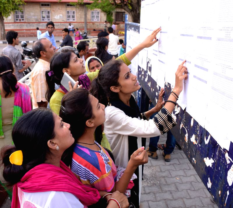 Parents and students check the notice board after the first cut-off list released at Maharani College in Jaipur on June 29, 2015.