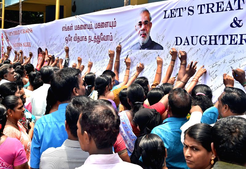 Parents sign on a huge flex measuring (80x6 ft) during an awareness campaign ' Restrict sons as you restrict daughter' at a private school in Chennai on Aug 20, 2014.