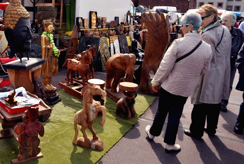 Customers choose wood carvings at a flea market in the suburb of Paris, France, April 20, 2014. Lots of local residents like going to flea market over the weekend to