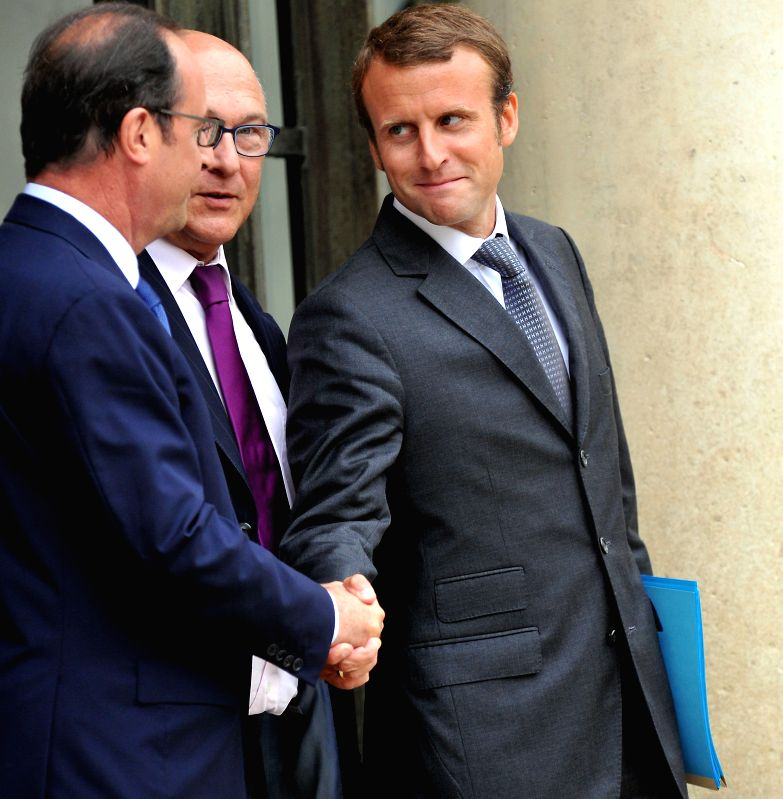 French President Francois Hollande (L) and France's new Economy Minister Emmanuel Macron (R) shake hands as French finance minister Michel Sapin looks on, as they ... - Emmanuel Macron