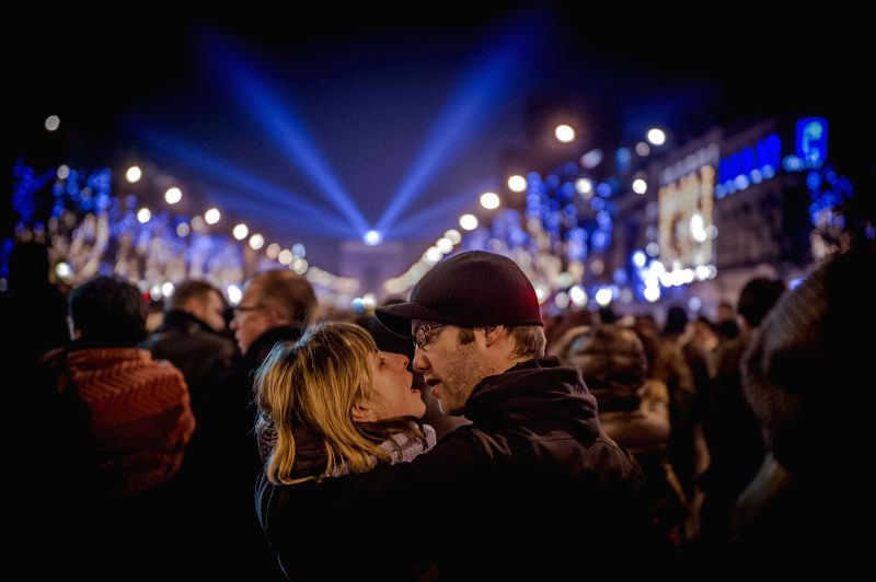 A couple waits for the fireworks as they celebrate the New Year's Eve on the Champs Elysees avenue in Paris, France, Dec. 31, 2014.